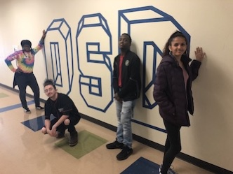 four high school students standing next to OSD wall mural.