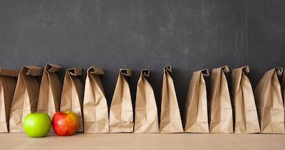 brown bags lined up with two apples in front.